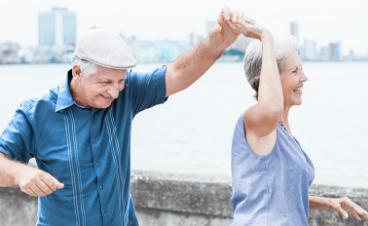 En endre mann og kvinne danser og har det gøt ute nær sjøen med en storby i bakgrunnen.